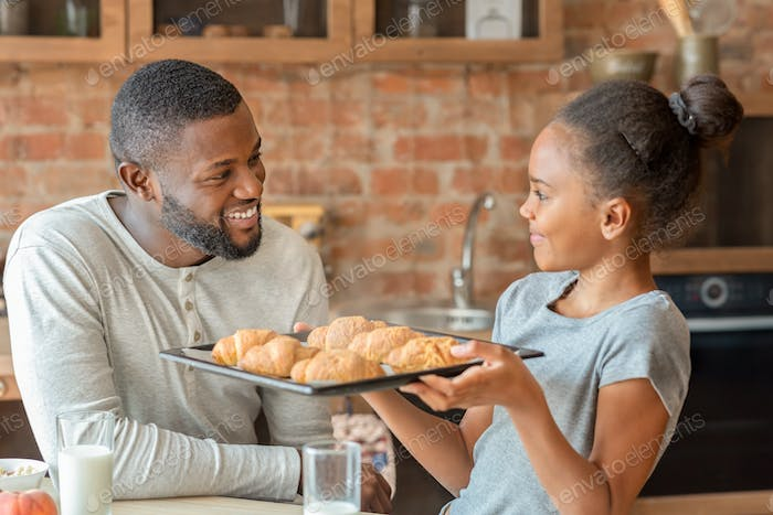 Adorable girl holding tray with freshly baked croissants