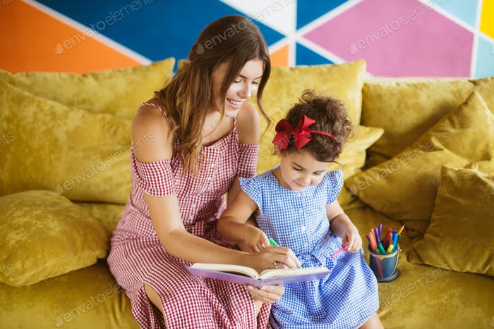 Beautiful mother with her little cute daughter in blue dress lea