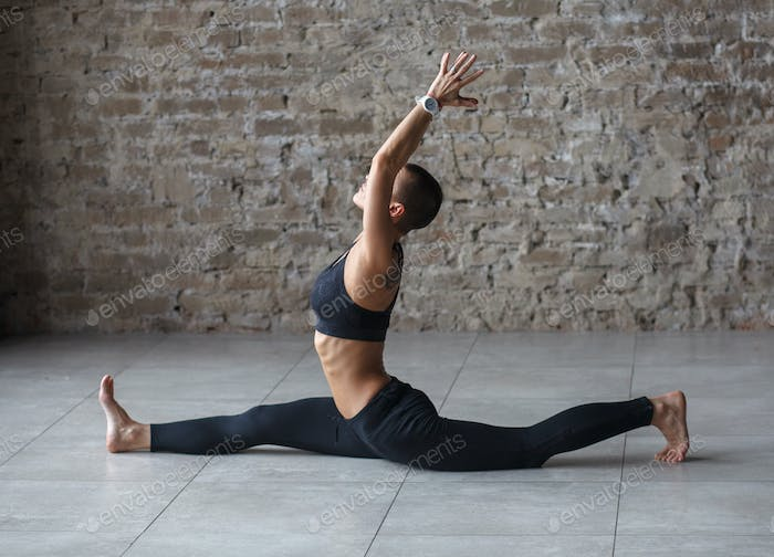 short haired woman doing yoga in loft interior