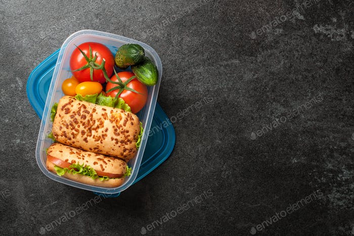 Lunch box with sandwiches and vegetables