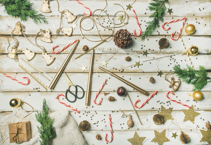 Flat-lay pattern of holiday decoration objects, toys, candles, candy canes