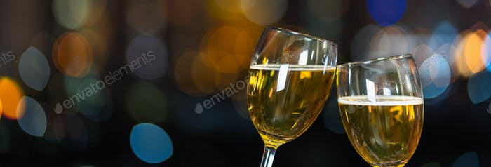 Tintineando con dos tazas de cerveza o vasos sobre la foto borrosa del paisaje urbano para celebrar,