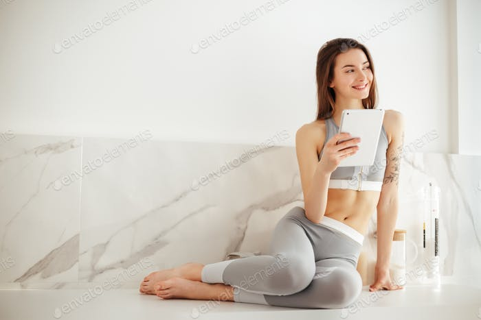 Cute smiling lady in sporty top and leggings sitting on floor with tablet joyfully looking aside