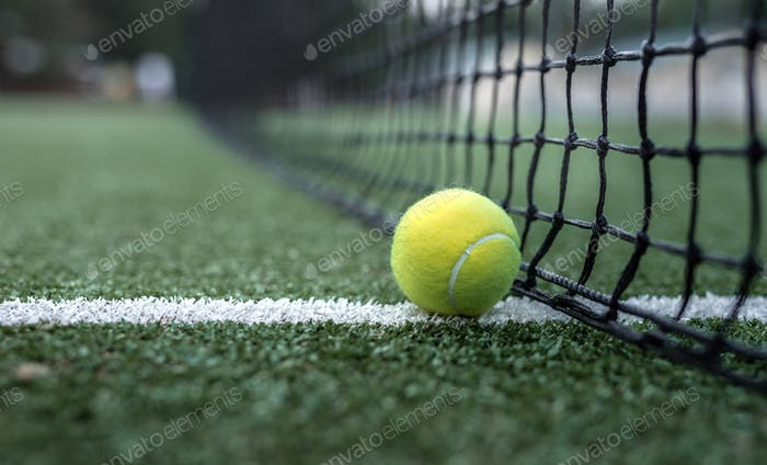 Yellow tennis ball at the net