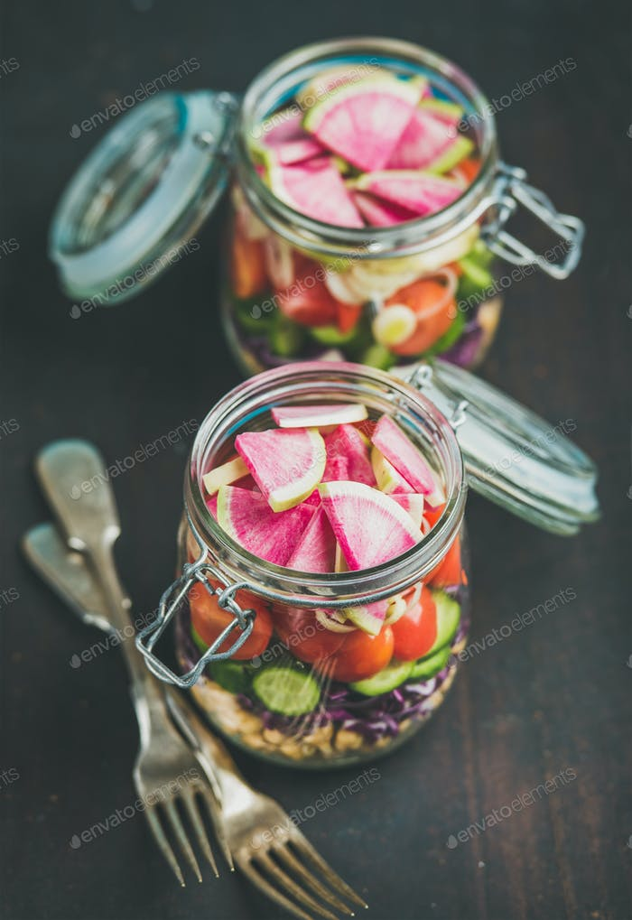 Vegetable and chickpea sprout vegan salad in jars, dark background