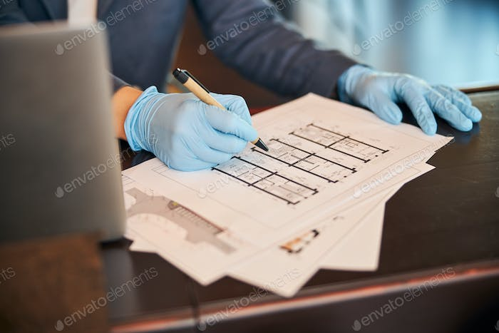 Businesswoman working on architectural plan in office