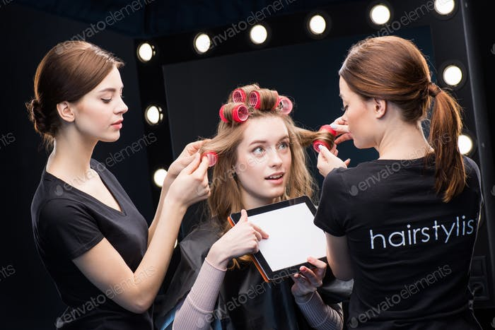 Two female hairstylists curling hair with curlers of beautiful young woman showing digital tablet
