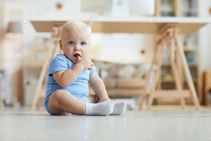 Entzückende Säugling sitzt auf dem Boden