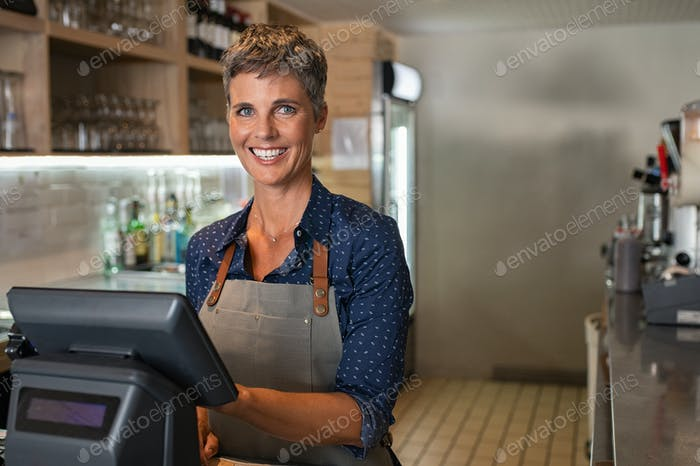 Owner at bar counter smiling