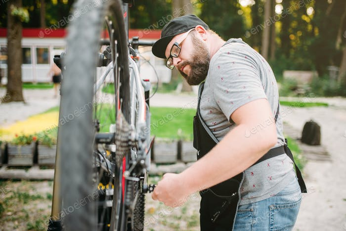 Repairman works with bike wheel, cycle workshop