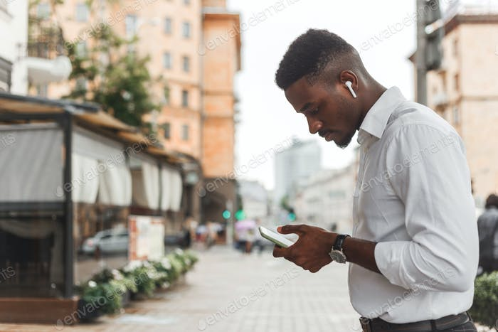 Outdoor portrait of modern young black african man with mobile phone in the street.