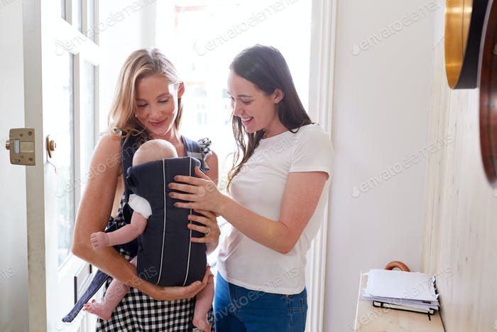 Same Sex Female Couple With Baby Daughter In Sling Opening Front Door Of Home