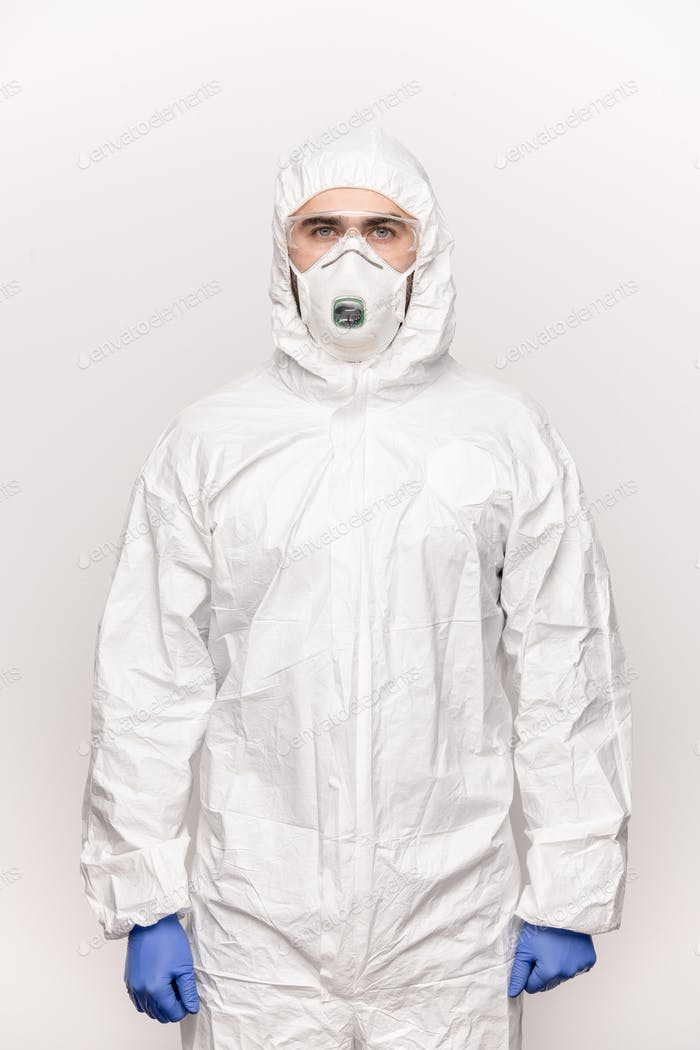 Contemporary young man in protective eyeglasses, blue gloves, mask and coveralls