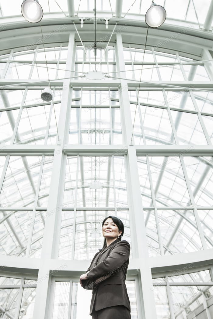 Asian business woman in a suit coat standing in a glass covered walkway