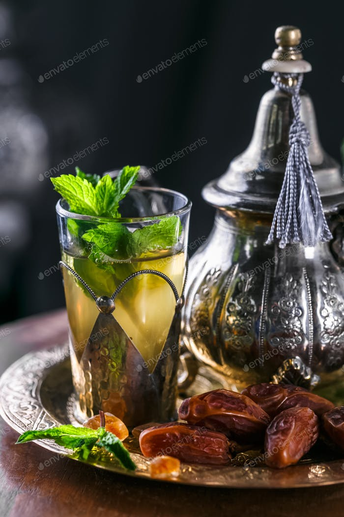 Glass of moroccan mint tea in traditional copper dishware, close view