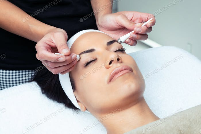 Cosmetologist making the eyes contour therapy for rejuvenation to woman on the spa center.