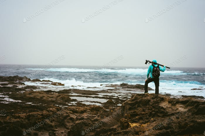 Photograph with tripod searching for good motive. Waves hitting volcanic rocky coastline. Santo