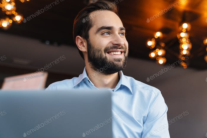 Portrait of young businessman using laptop while working in office