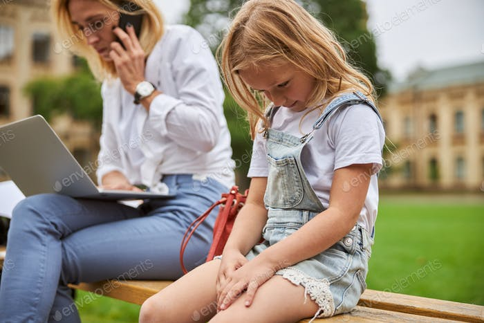 Woman with little girl working on a laptop in nature
