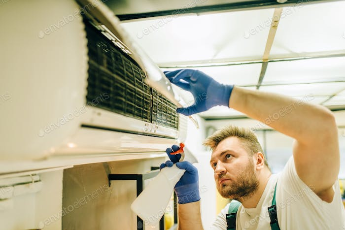 Repairman in uniform cleans the air conditioner