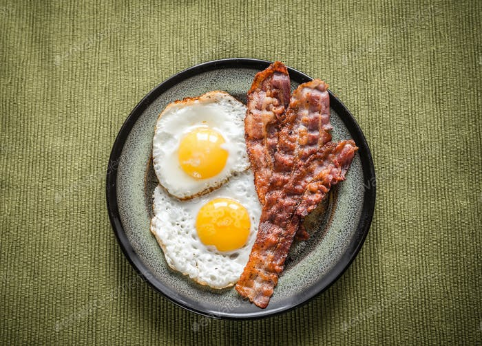 Portion of fried eggs with bacon