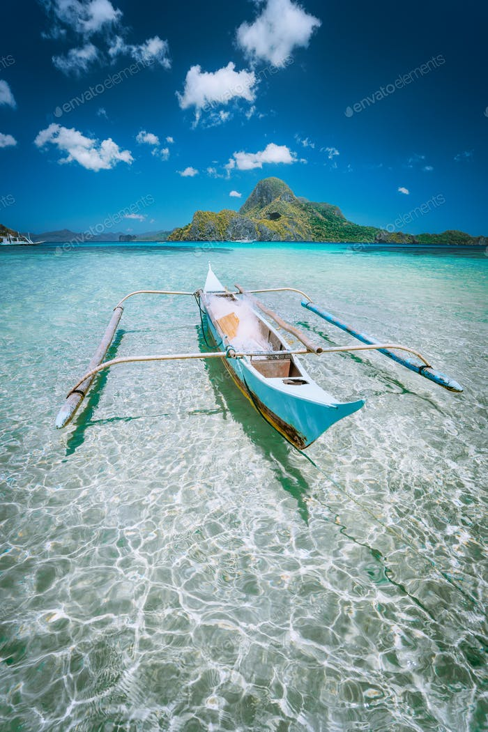 Traditional filippino fisher banca boat in blue lagoon at El Nido bay with Cadlao Island on