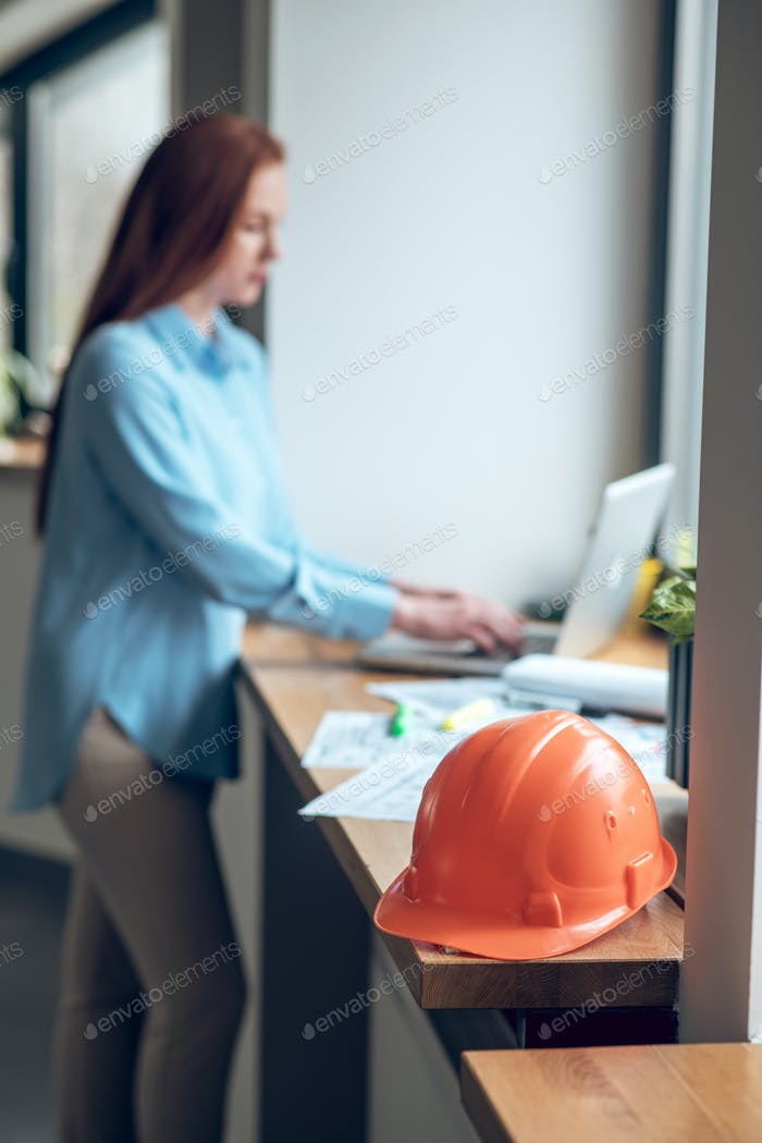 Protective helmet on windowsill and woman working on laptop