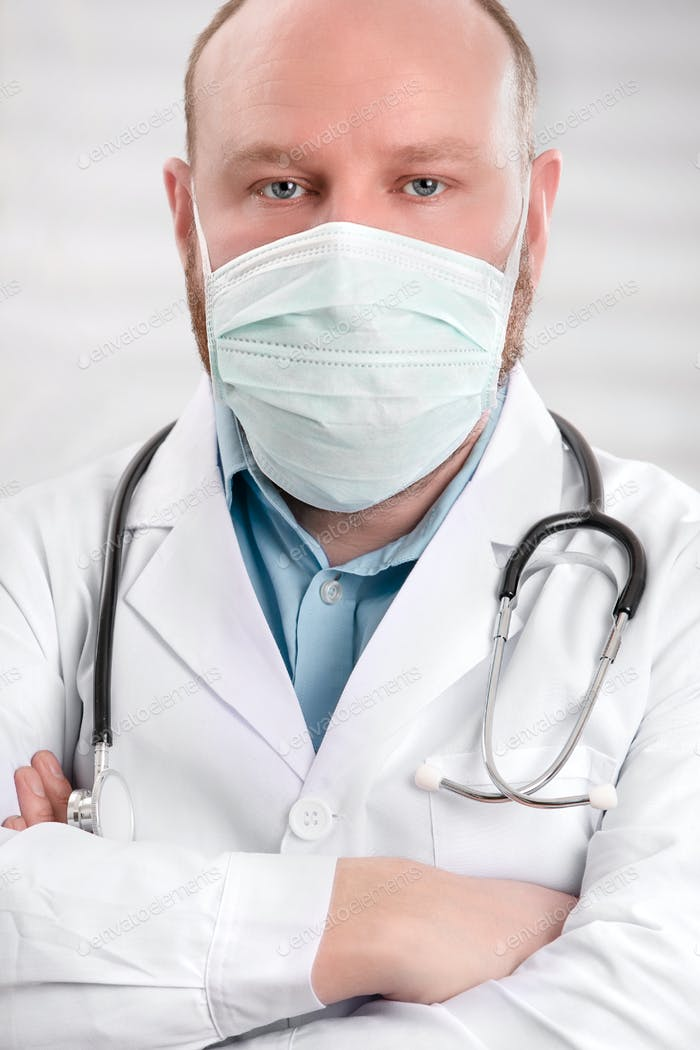 Portrait of a serious doctor wearing protective face mask and stethoscope