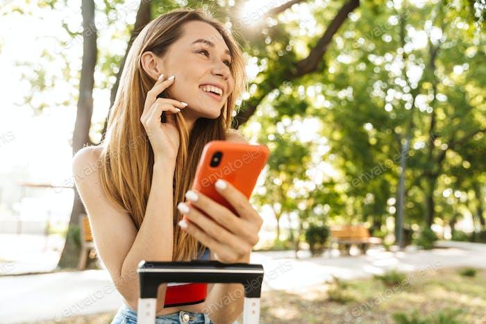 Foto von attraktiven Touristenmädchen lächelnd und hält Smartphone im Park