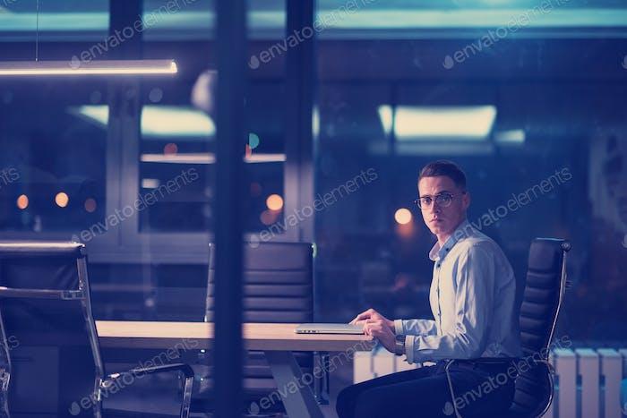 Mann arbeitet auf Laptop im dunklen Büro