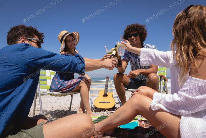 Friends toasting drinks and having fun at beach