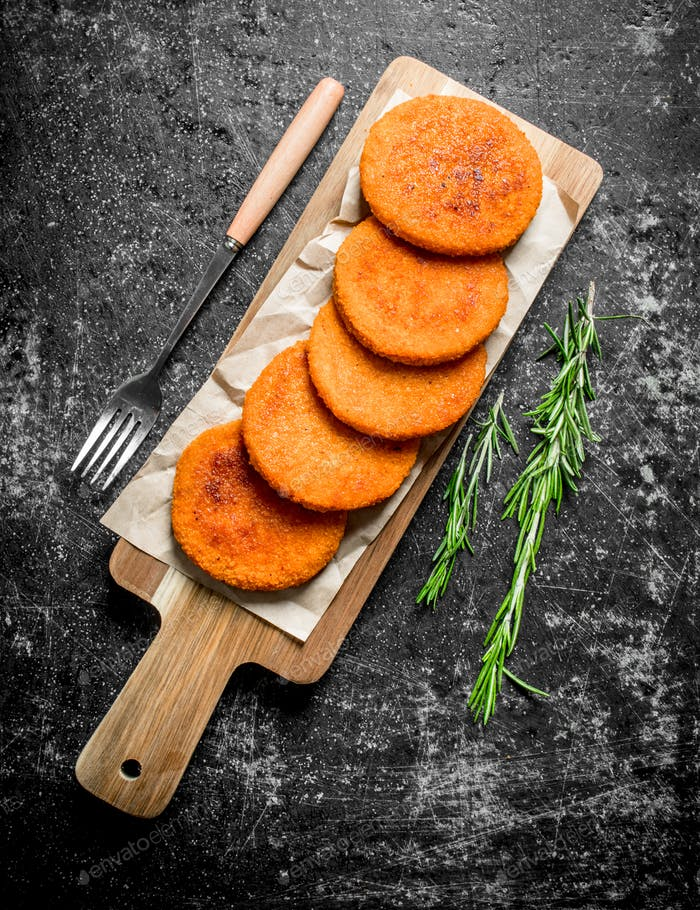 Fish cutlets on paper with fork and rosemary.