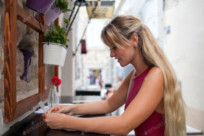 Beautiful tourist woman in local restaurant outdoor looking at menu, travel lifestyle