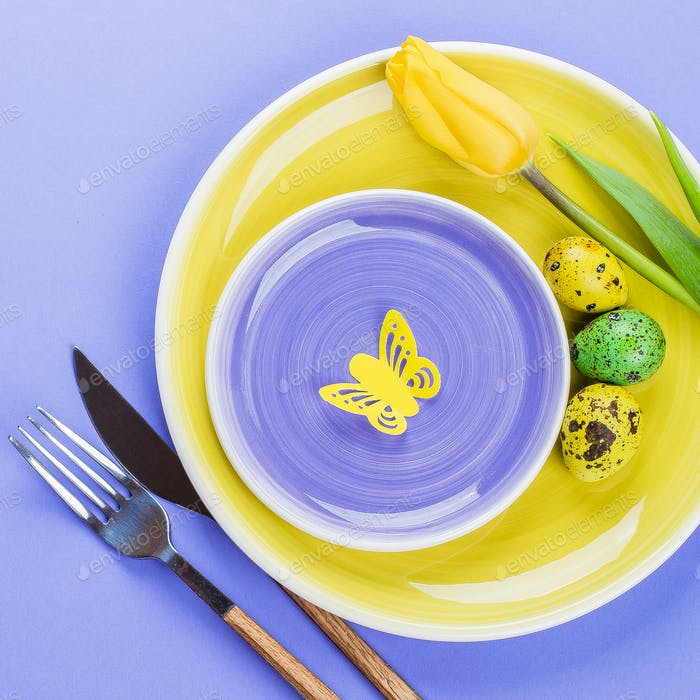 Easter table setting with spring tulips, colorful quail eggs and cutlery on paper background