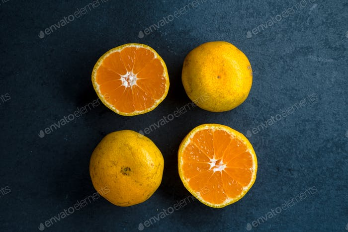 Four halves of an orange on a blue stone