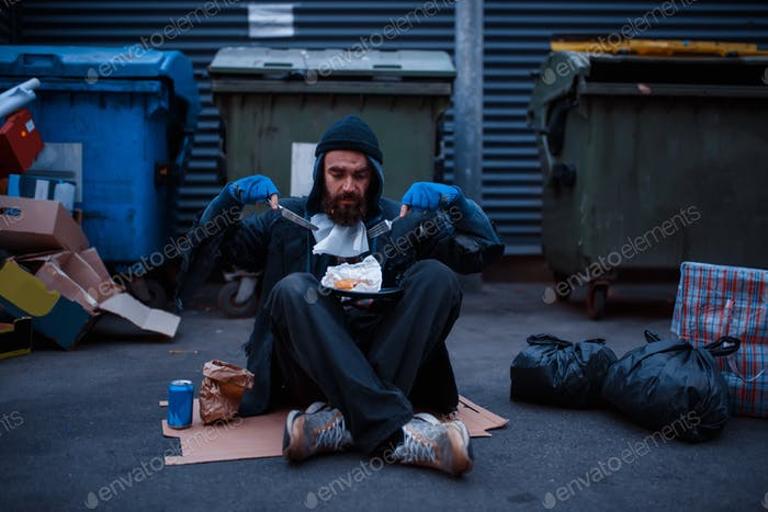 Dirty beggar with knife and fork eats at trashcan