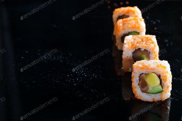 California Maki Sushi mit Masago - Rolle aus Krabbenfleisch, Avocado, Gurke auf Glas schwarz