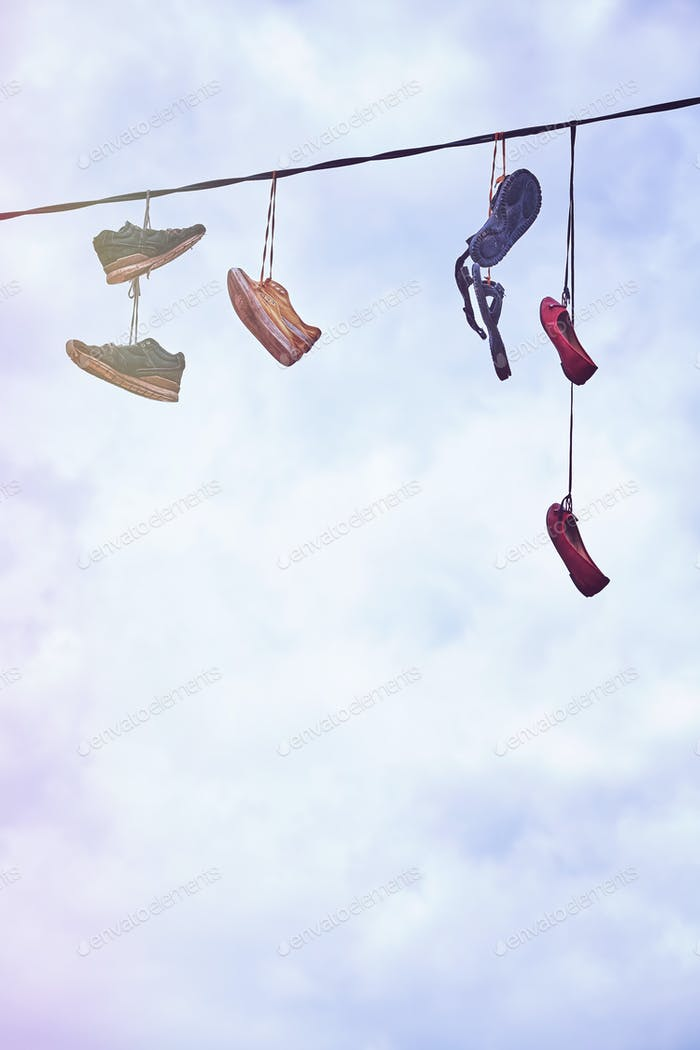 Old dirty shoes hanging on wire.