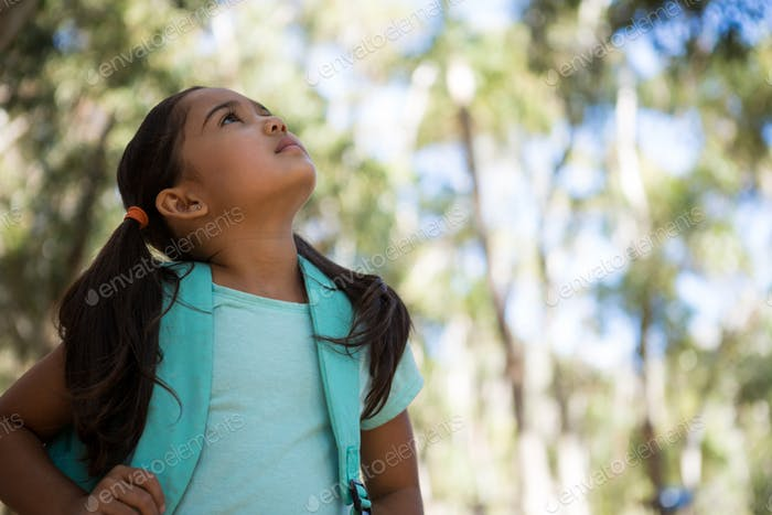 Little girl standing with backpack looking up in the sky