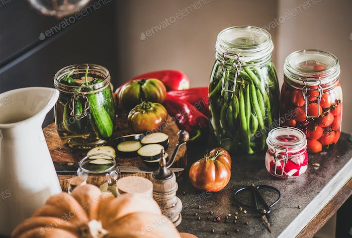 Ingredients and jars with homemade vegetables preserves on concrete table