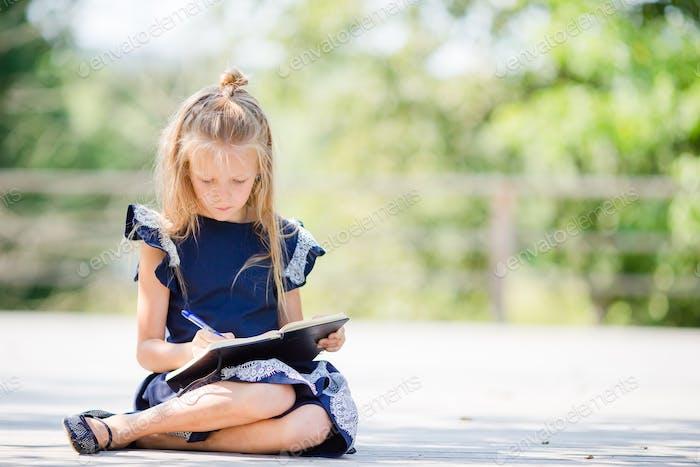 Entzückende kleine Schulmädchen mit Notizen und Bleistiften im Freien. Zurück zur Schule