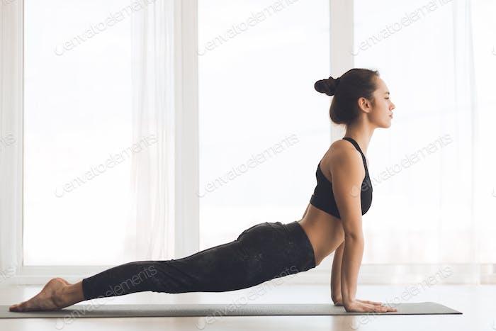 Woman doing cobra pose at modern studio