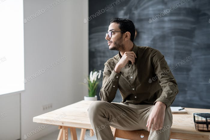 Restful male employee in eyeglasses and casualwear looking through office window