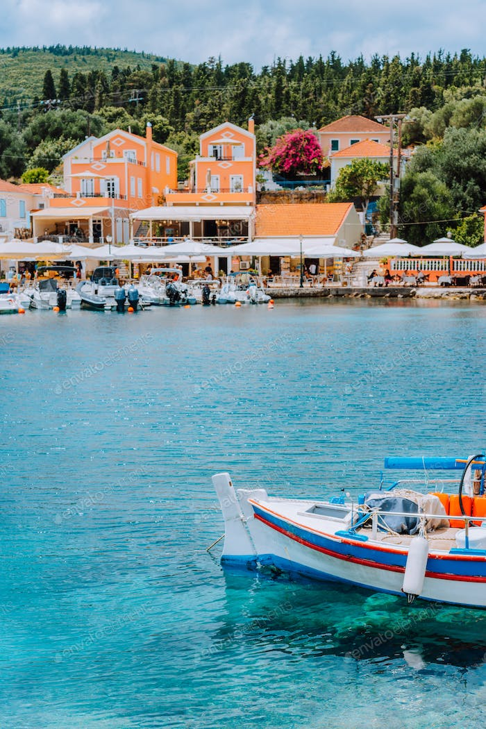 Traditional colorful Greek fishing boat in front of picturesque village, Greece