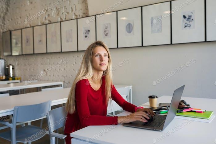 молодой человек, работающий на ноутбуке в кабинете