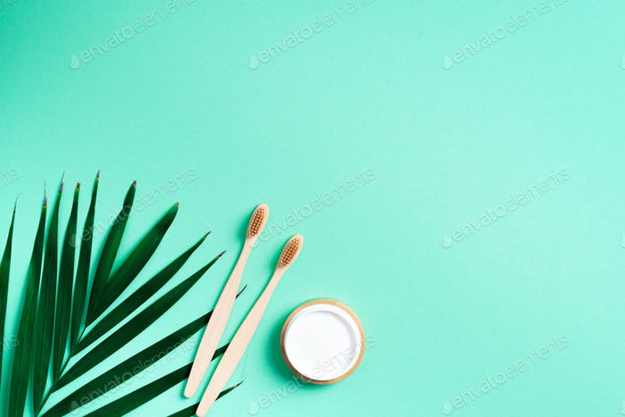 .Alternative health care concept. Natural toothpaste and wood toothbrush on trendy green background