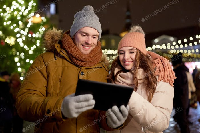 happy couple with tablet pc at christmas market