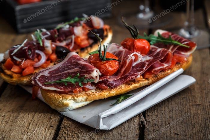 Toast mit ruckeligem Fleisch auf einem Stück Papier. Rustikale Oberfläche aus Holz Tischplatte im Hintergrund.