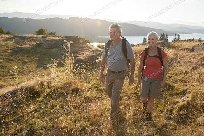 Senior Couple Walking On Top Of Hill On Hike Through Countryside In Lake District UK