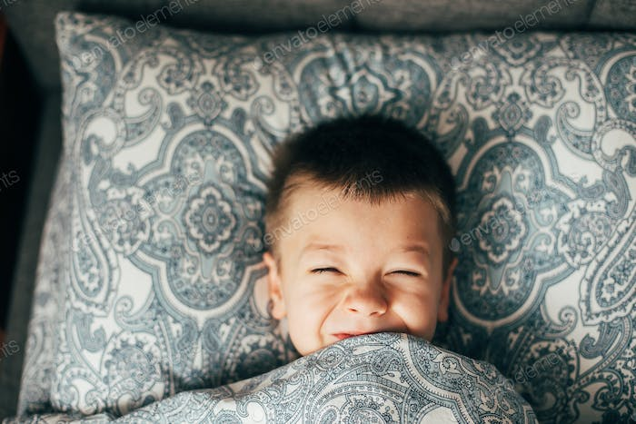 Cute happy child boy smiling, having fun in bed at home. Lifestyle, authentic moment